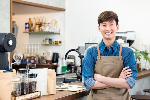 Vrolijke jonge aziatische mensenondernemer in koffiewinkel