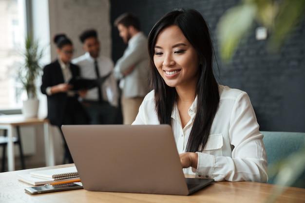 Vrolijke jonge aziatische onderneemster die laptop met behulp van