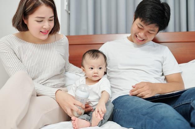 Vrolijke jonge aziatische ouders zitten in bed, spelen met kleine baby en voeden haar met formule
