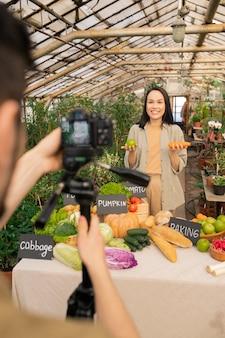 Vrolijke jonge aziatische vrouw die appel en wortel houdt terwijl ze een gezond recept deelt met volgers die video opnemen voor sociale media