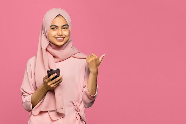 Vrolijke jonge aziatische vrouw die een smartphone gebruikt en met vinger richt om ruimte te kopiëren