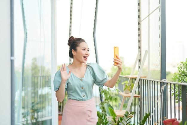 Vrolijke jonge aziatische vrouw die een videogesprek met haar telefoon heeft wanneer zij zich op een balkon bevindt