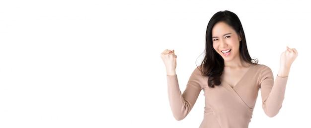 Vrolijke jonge aziatische vrouw die haar vuisten met opgetogen gezicht opheft, ja gebaar