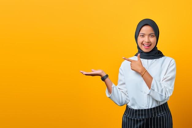Vrolijke jonge aziatische vrouw die product presenteert en met de vingers op gele achtergrond wijst