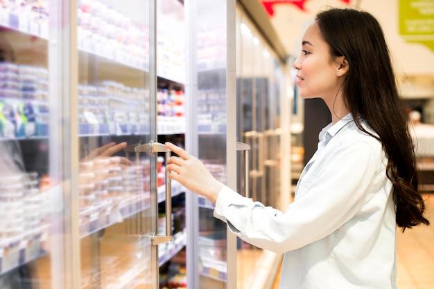 Vrolijke jonge aziatische vrouw die zuivelproducten kiezen bij supermarkt