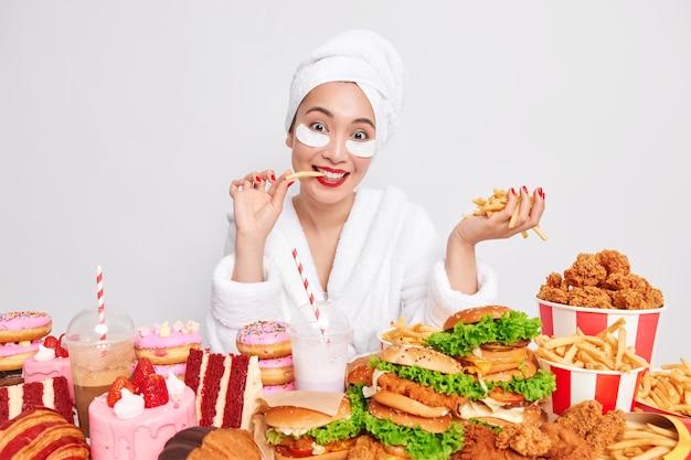Vrolijke jonge aziatische vrouw eet heerlijke smakelijke franse vriend heeft slechte eetgewoonten
