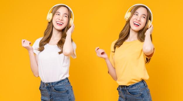 Vrolijke jonge aziatische vrouw in koptelefoon luisteren naar muziek en genieten van favoriete playlist-applicatie met dansen op oranje achtergrond.
