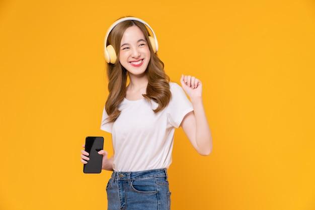 Vrolijke jonge aziatische vrouw in koptelefoon luisteren naar muziek en genieten van favoriete playlist-applicatie op smartphone met dansen op oranje achtergrond.