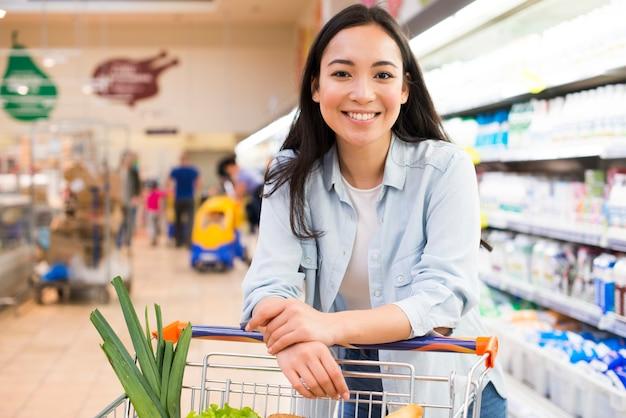 Vrolijke jonge aziatische vrouw met boodschappenwagentje bij supermarkt