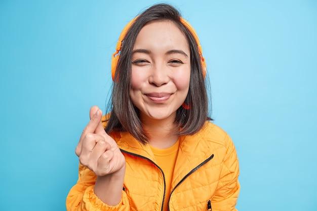 Vrolijke jonge aziatische vrouw met donker haar toont koreaans als teken dat liefde uitdrukt, gekleed in jas, luistert naar audiotrack via koptelefoon geïsoleerd over blauwe muur. lichaamstaal concept