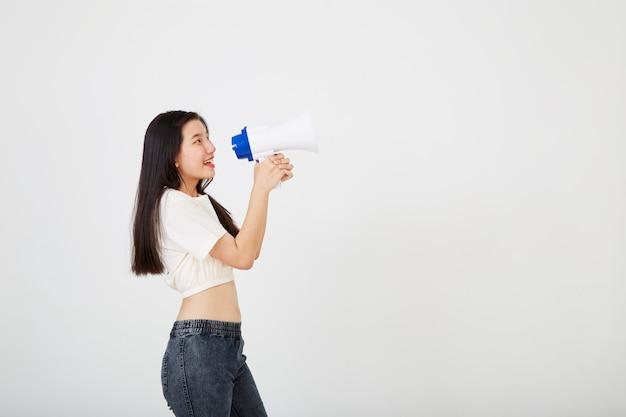Vrolijke jonge aziatische vrouw met megafoonaankondiging in geïsoleerde studio