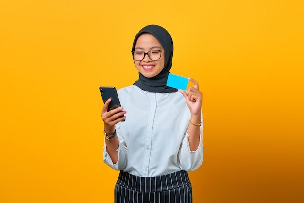 Vrolijke jonge aziatische vrouw met mobiele telefoon en creditcard op gele achtergrond
