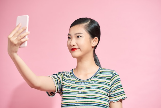 Vrolijke jonge aziatische vrouw met mobiele telefoon en selfie maken op roze