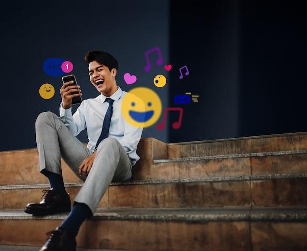 Vrolijke jonge aziatische zakenman met behulp van mobiele telefoon in de stad. genieten van social media-applicatie. omgeven door vele pictogrammen