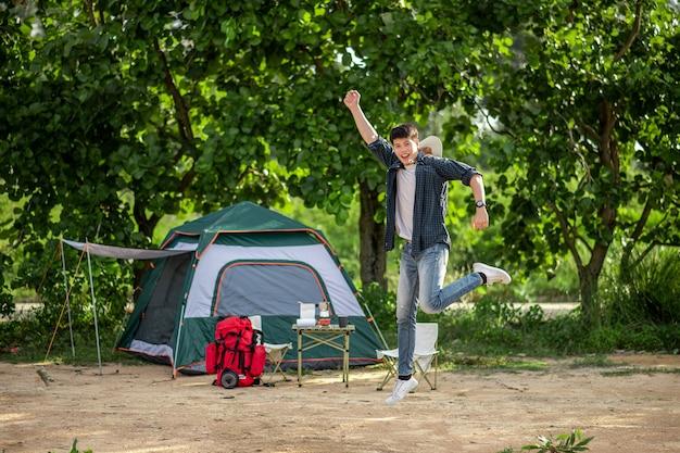 Vrolijke jonge backpacker man springen en glimlachen aan de voorkant van de tent in het bos met koffieset en het maken van verse koffiemolen tijdens het kamperen op zomervakantie