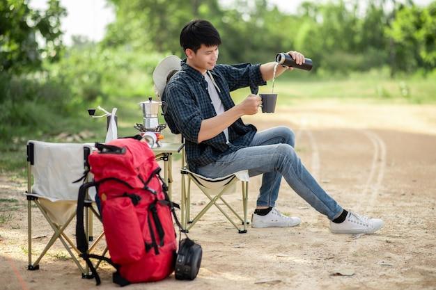 Vrolijke jonge backpacker man zit aan de voorkant van de tent in het bos met koffieset en het maken van verse koffiemolen tijdens het kamperen op zomervakantie