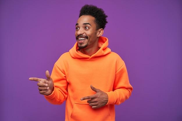 Vrolijke jonge bebaarde donkere huid krullend brunette man wijsvingers verhogen en opzij kijken met brede vrolijke glimlach, gekleed in oranje hoodie op paars