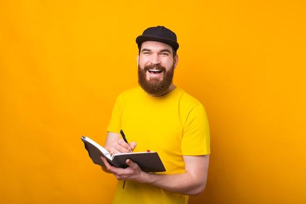 Vrolijke jonge bebaarde hipster man in agenda schrijven en glimlachen