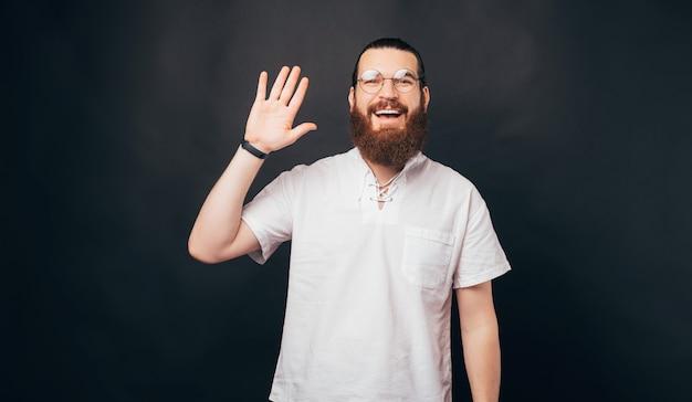 Vrolijke jonge bebaarde hipster man met ronde bril en hallo gebaar maken, zwaaiend met de hand