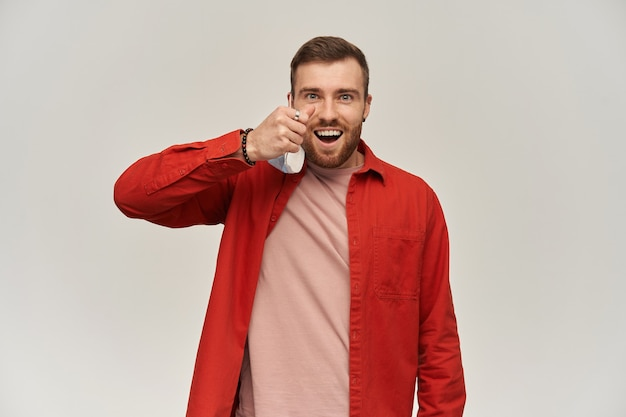 Vrolijke jonge bebaarde man in rood shirt staande en opstijgen virus beschermend masker tegen coronavirus van zijn gezicht over witte muur