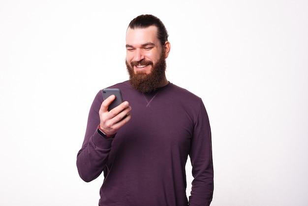 Vrolijke jonge bebaarde man kijkt en lacht in zijn telefoon in de buurt van een witte muur