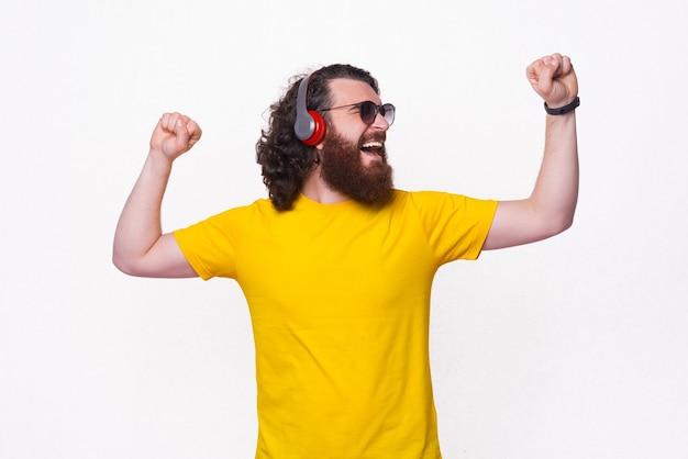 Vrolijke jonge bebaarde man met gele t-shirt dansen en muziek luisteren op rode koptelefoon