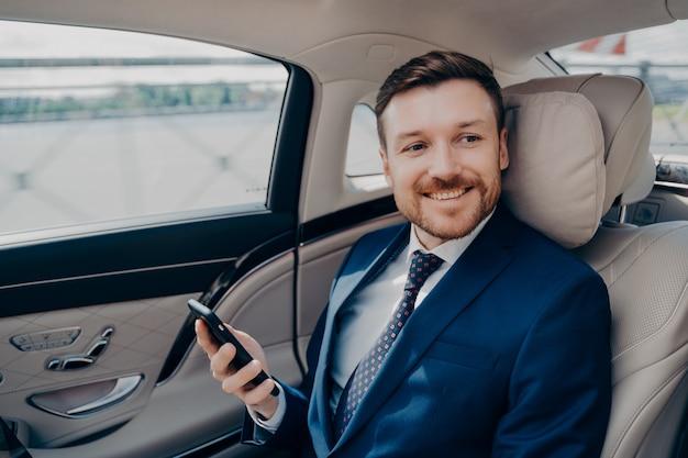 Vrolijke jonge bedrijfsleider in elegante dure smoking rijdt in luxe auto met chauffeur van het bedrijf naar financiële bijeenkomst terwijl hij marktaandelenkoersen en indices op zijn mobiel controleert