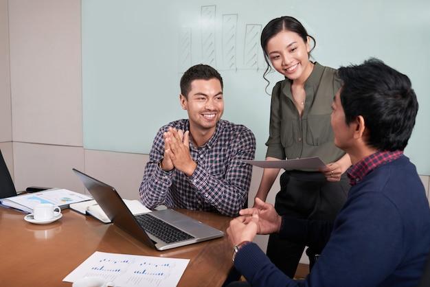 Vrolijke jonge bedrijfsmensen die grafieken en diagrammen in de conferentieruimte bespreken