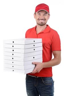 Vrolijke jonge bezorger die een pizzadoos houdt.
