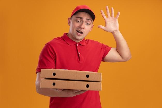 Vrolijke jonge bezorger die eenvormig met glb draagt die pizzadozen houdt die hallo gebaar tonen dat op oranje muur wordt geïsoleerd