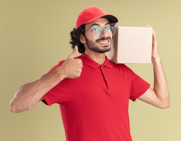 Vrolijke jonge bezorger in rood uniform en pet met een bril die een kartonnen doos op de schouder houdt en naar de voorkant kijkt met duim omhoog geïsoleerd op een olijfgroene muur