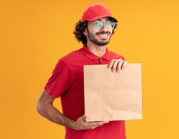 Vrolijke jonge bezorger in rood uniform en pet met een bril die een papieren pakket vasthoudt en kijkt naar de voorkant geïsoleerd op een oranje muur