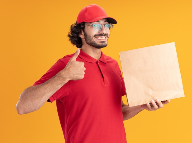 Vrolijke jonge bezorger in rood uniform en pet met een bril die een papieren pakket vasthoudt en naar de voorkant kijkt met duim omhoog geïsoleerd op een oranje muur