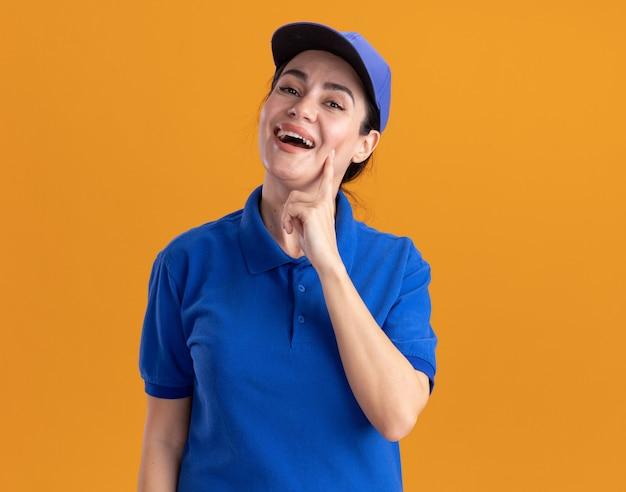 Vrolijke jonge bezorger in uniform en pet die naar de voorkant kijkt en het gezicht aanraakt met vinger geïsoleerd op een oranje muur met kopieerruimte