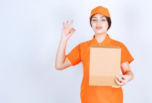 Vrolijke jonge bezorger op witte muur terwijl ze een open doos vasthoudt