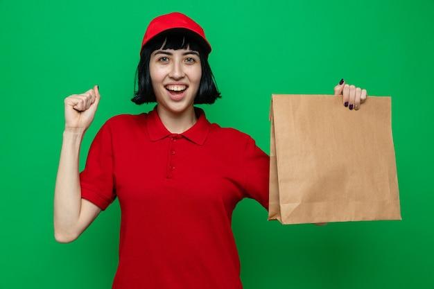 Vrolijke jonge blanke bezorger die voedselverpakking vasthoudt en haar vuist omhoog houdt