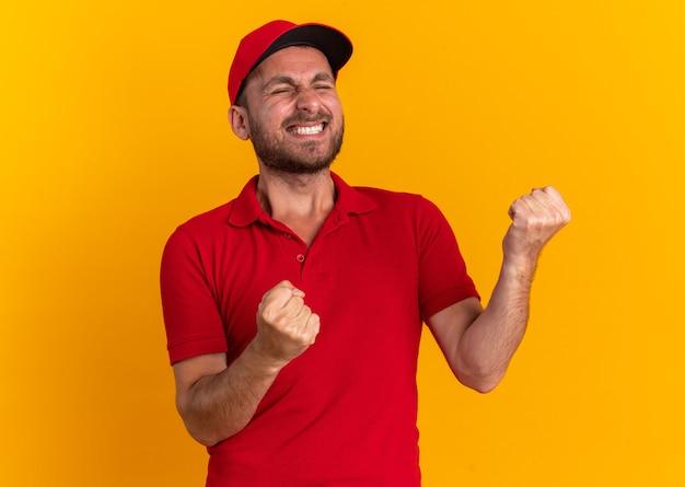 Vrolijke jonge blanke bezorger in rood uniform en pet doet ja gebaar met gesloten ogen