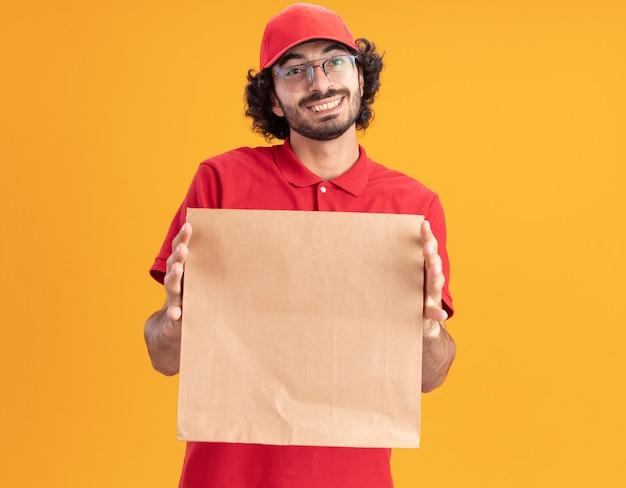 Vrolijke jonge blanke bezorger in rood uniform en pet met een bril die een papieren pakket uitrekt dat op een oranje muur met kopieerruimte is geïsoleerd