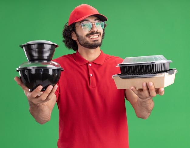 Vrolijke jonge blanke bezorger in rood uniform en pet met een bril die een papieren voedselpakket en voedselcontainers uitrekt die op een groene muur zijn geïsoleerd
