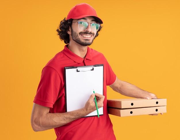 Vrolijke jonge blanke bezorger in rood uniform en pet met een bril die pizzapakketten vasthoudt die met potlood naar het klembord wijzen
