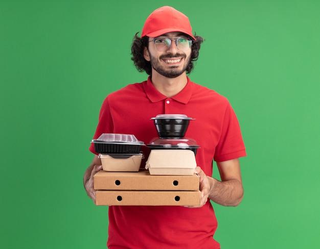 Vrolijke jonge blanke bezorger in rood uniform en pet met een bril met pizzapakketten met papieren voedselpakketten en voedselcontainers erop kijkend naar de voorkant