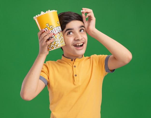 Vrolijke jonge blanke jongen die een emmer popcorn en een stuk popcorn vasthoudt en het hoofd aanraakt met een emmer popcorn en de hand omhoog kijkt