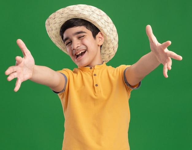 Vrolijke jonge blanke jongen met strandhoed die handen uitspreidt die knipogen