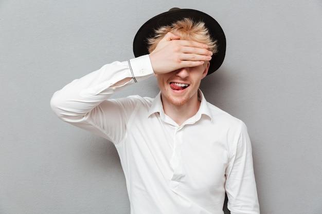 Vrolijke jonge blanke man die ogen met de hand