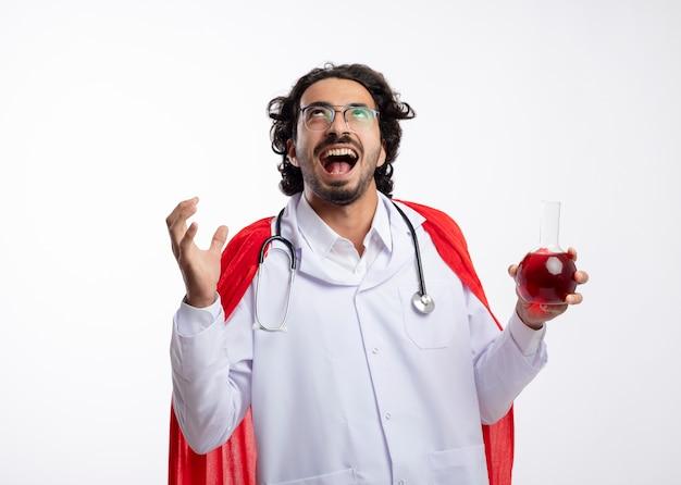 Vrolijke jonge blanke man in optische bril dragen arts uniform met rode mantel en met een stethoscoop om de nek staat met opgeheven hand en houdt rode chemische vloeistof in glazen kolf
