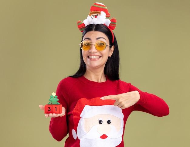 Vrolijke jonge blanke meisje dragen hoofdband van de kerstman en trui met bril houden en wijzend op kerstboom speelgoed met datum kijken camera geïsoleerd op olijfgroene achtergrond