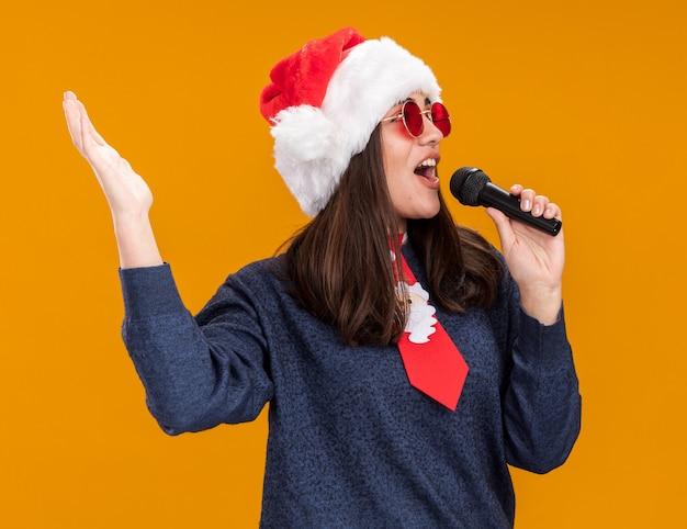 Vrolijke jonge blanke meisje in zonnebril met kerstmuts en santa stropdas houdt microfoon doen alsof te zingen kijkend naar kant geïsoleerd op oranje muur met kopie ruimte