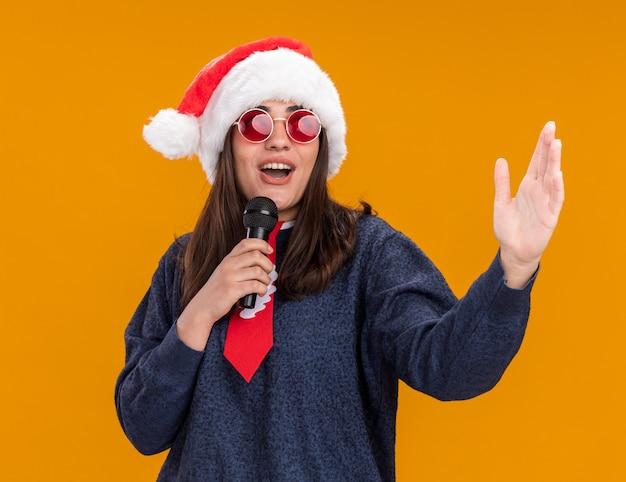 Vrolijke jonge blanke meisje in zonnebril met kerstmuts en santa stropdas houdt microfoon en staat met opgeheven hand geïsoleerd op oranje muur met kopie ruimte