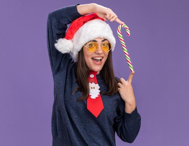 Vrolijke jonge blanke meisje in zonnebril met kerstmuts en santa stropdas houdt snoepgoed geïsoleerd op paarse muur met kopieerruimte