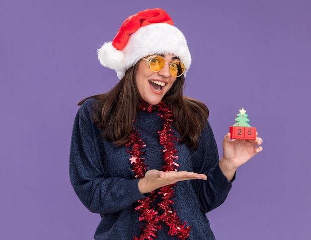 Vrolijke jonge blanke meisje in zonnebril met kerstmuts en slinger om nek houdt en wijst naar kerstboom ornament geïsoleerd op paarse muur met kopie ruimte